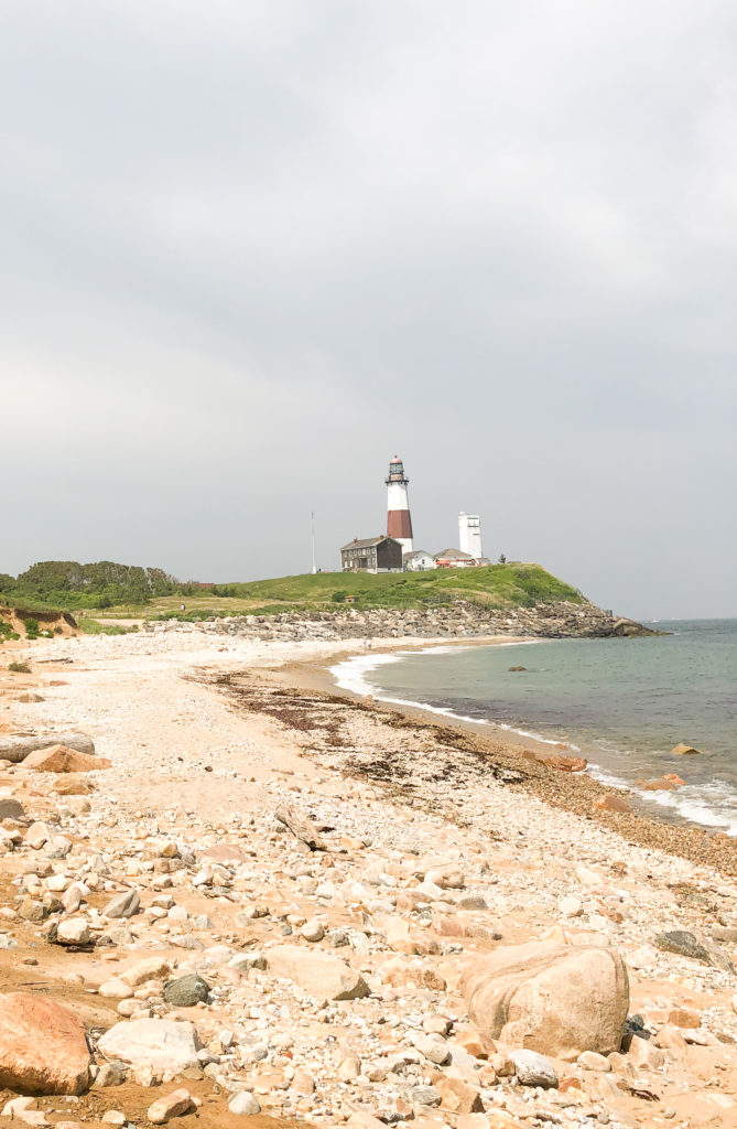 A rocky beach leading to a lighthouse in Montauk, a popular road trip destination