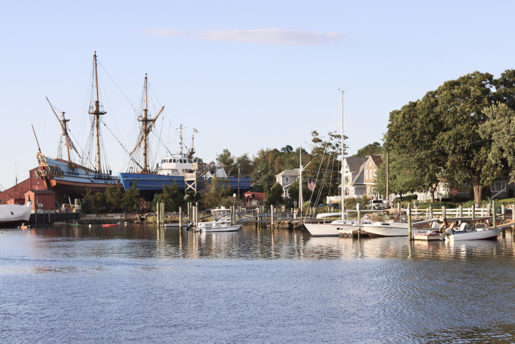 A river lined with historic ships in Mystic, a popular summer road trip destination