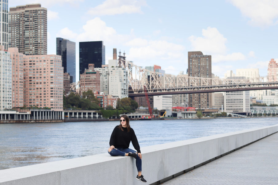 A woman sitting on a ledge with the NYC skyline and Ed Koch bridge in the background.