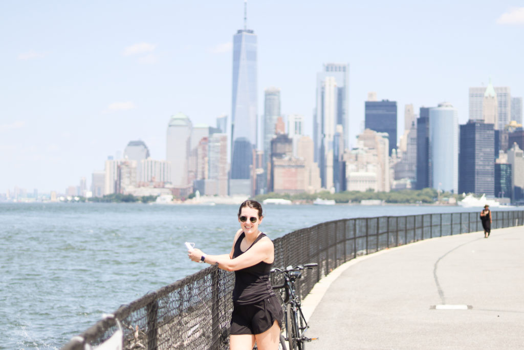 A woman standing on Governor's Island with the Manhattan skyline in the background.