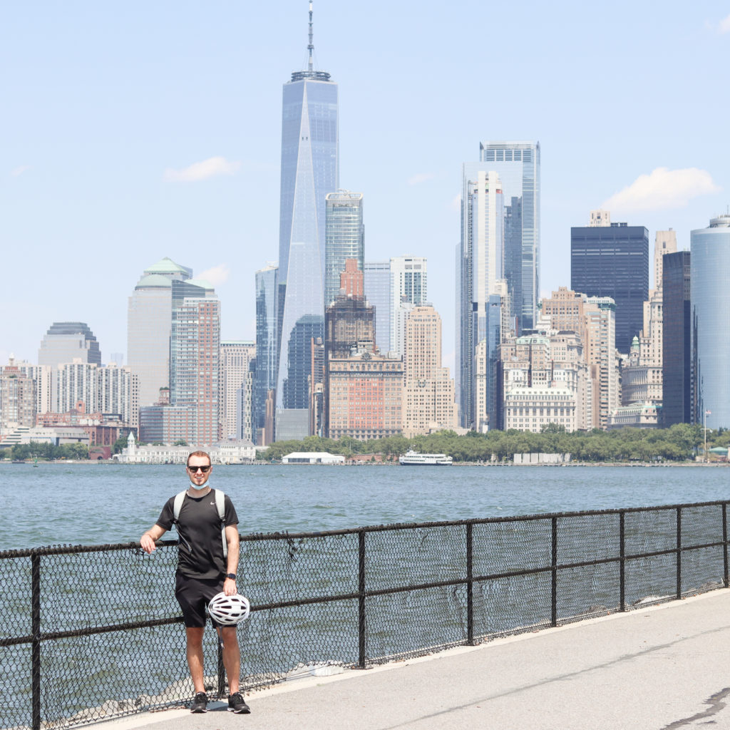 A man standing on Governor's Island with the Manhattan skyline in the background.