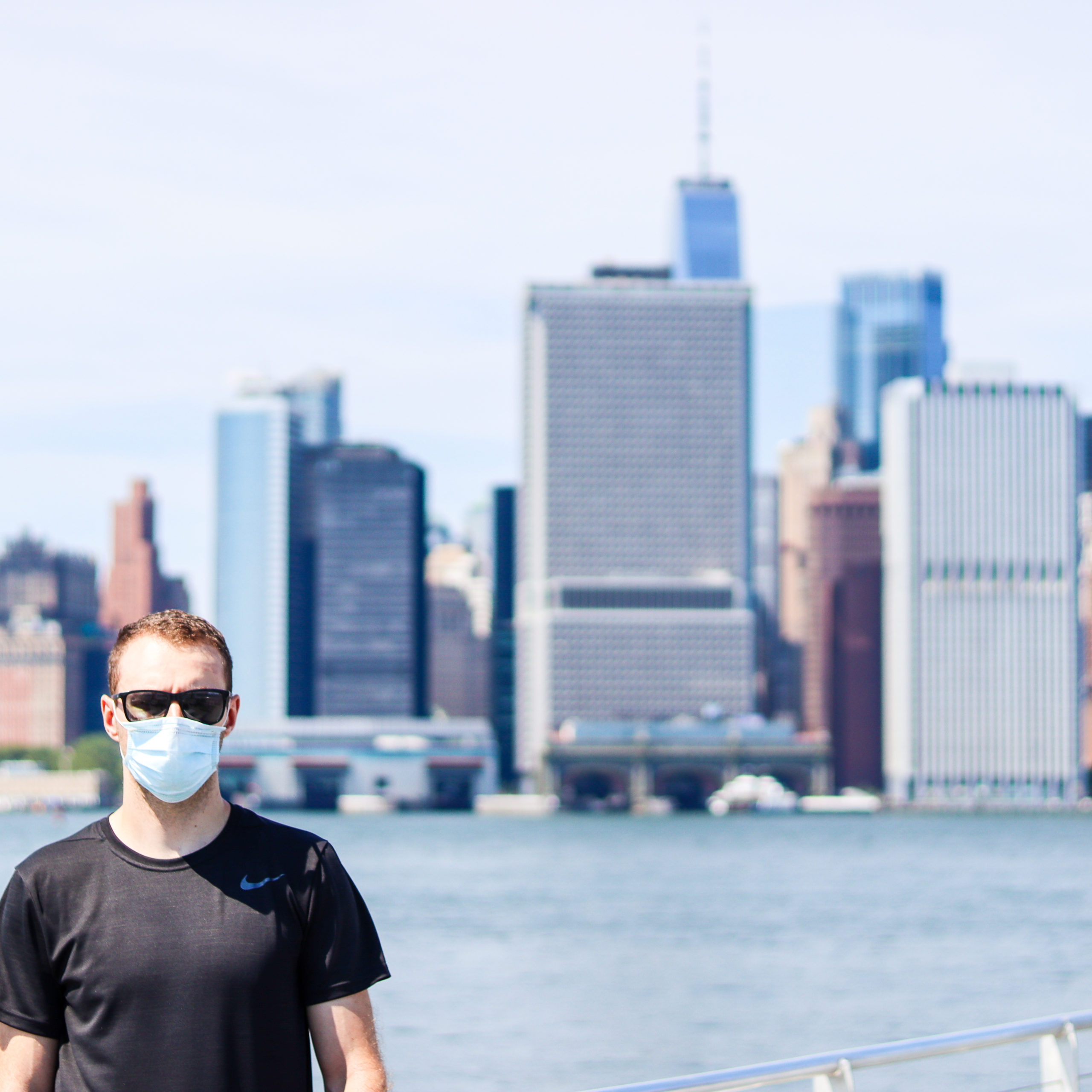 Man standing in front of Manhattan skyline view from Governors Island