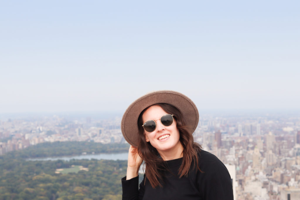 Women holding onto her hat with the Central Park skyline in the background.