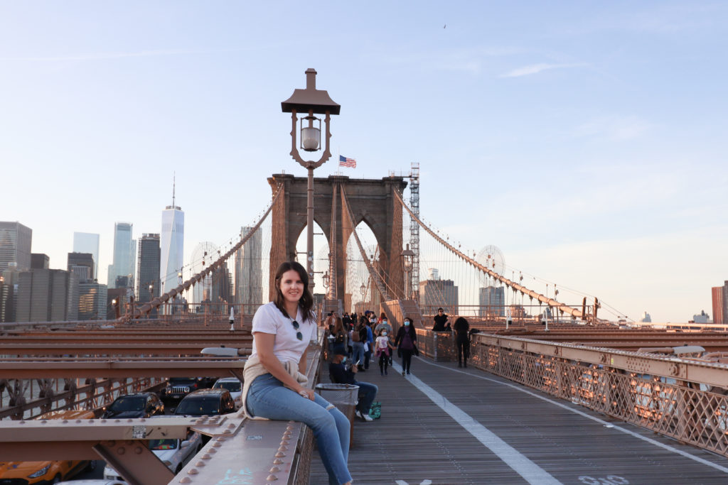 Women sitting on the Brooklyn Bridge with the Manhattan skyline in the background.