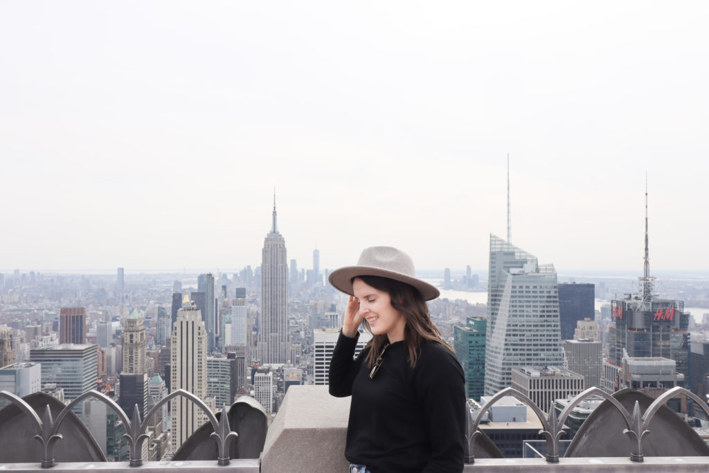 Women holding onto her hat with the Manhattan skyline in the background.