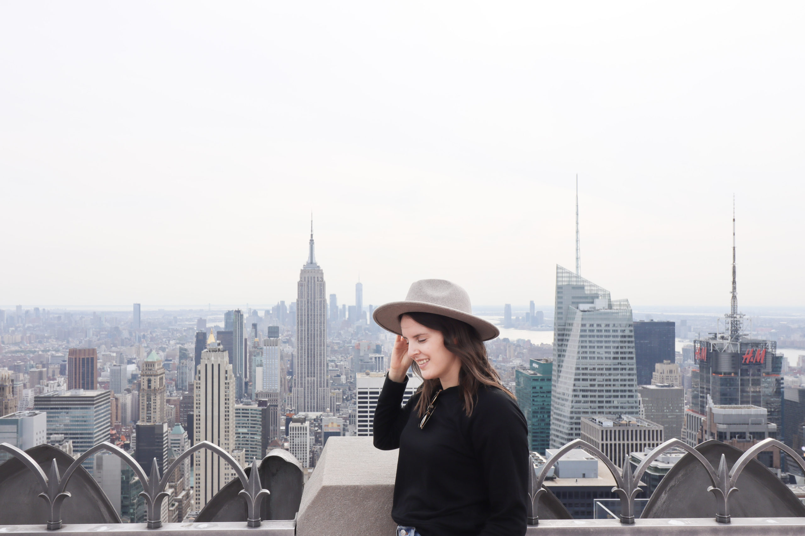 Woman looking at the Empire State building from Top of the Rock, one of the Instagram spots in NYC