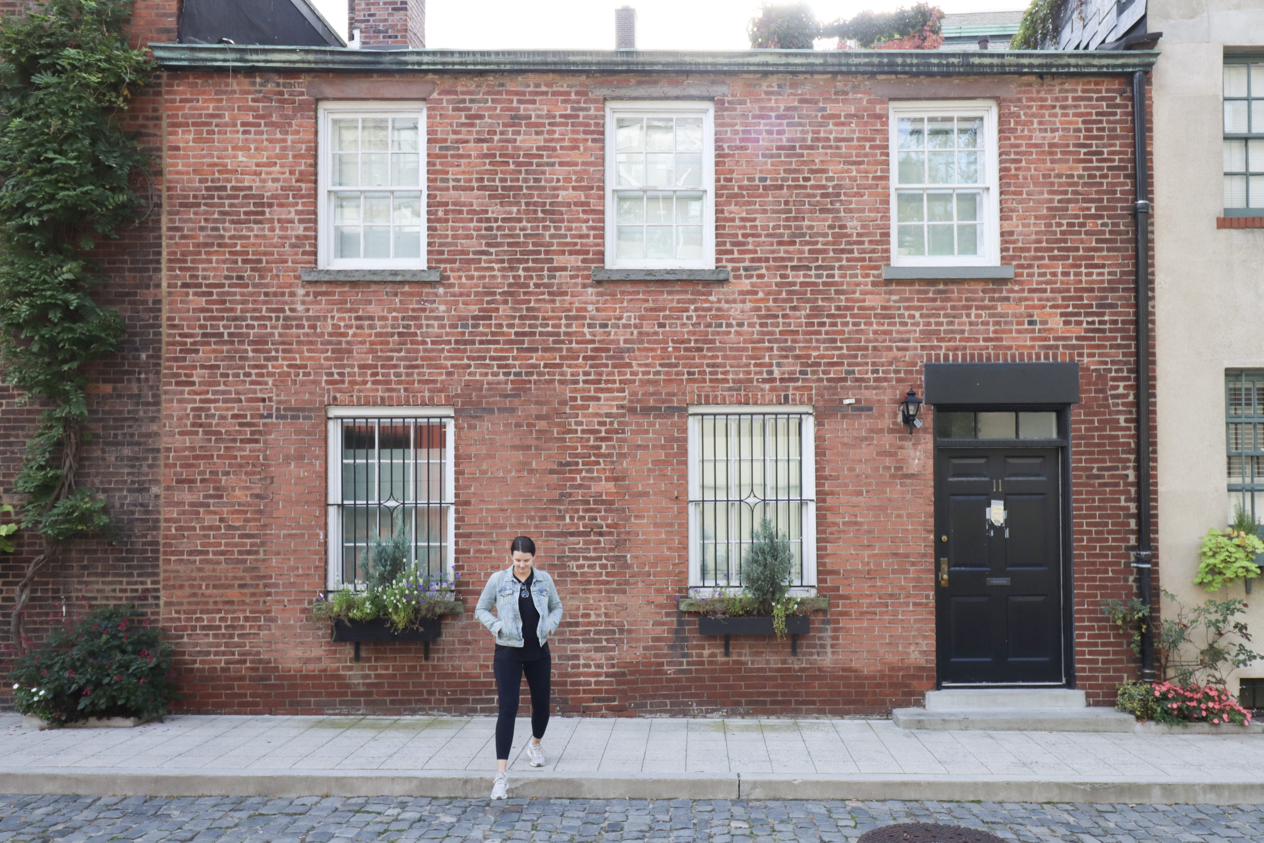 Woman standing in Washington Mews, one of the Instagram spots in NYC