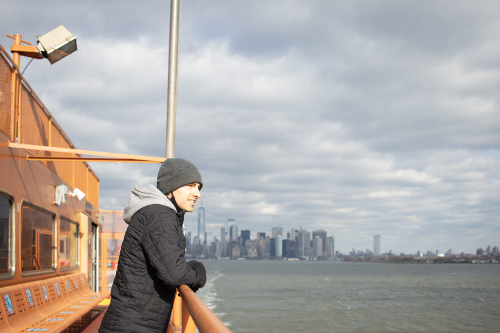 A man standing on the Staten Island Ferry with the Manhattan skyline view in the background.