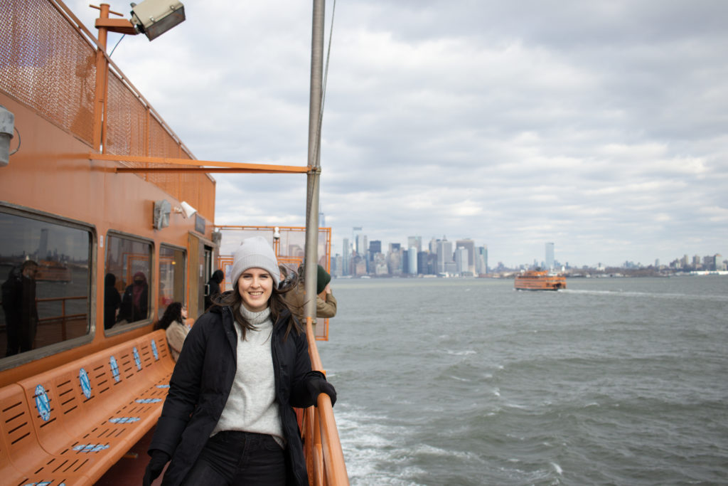 A woman on the Staten Island Ferry with the Manhattan skyline in the background.
