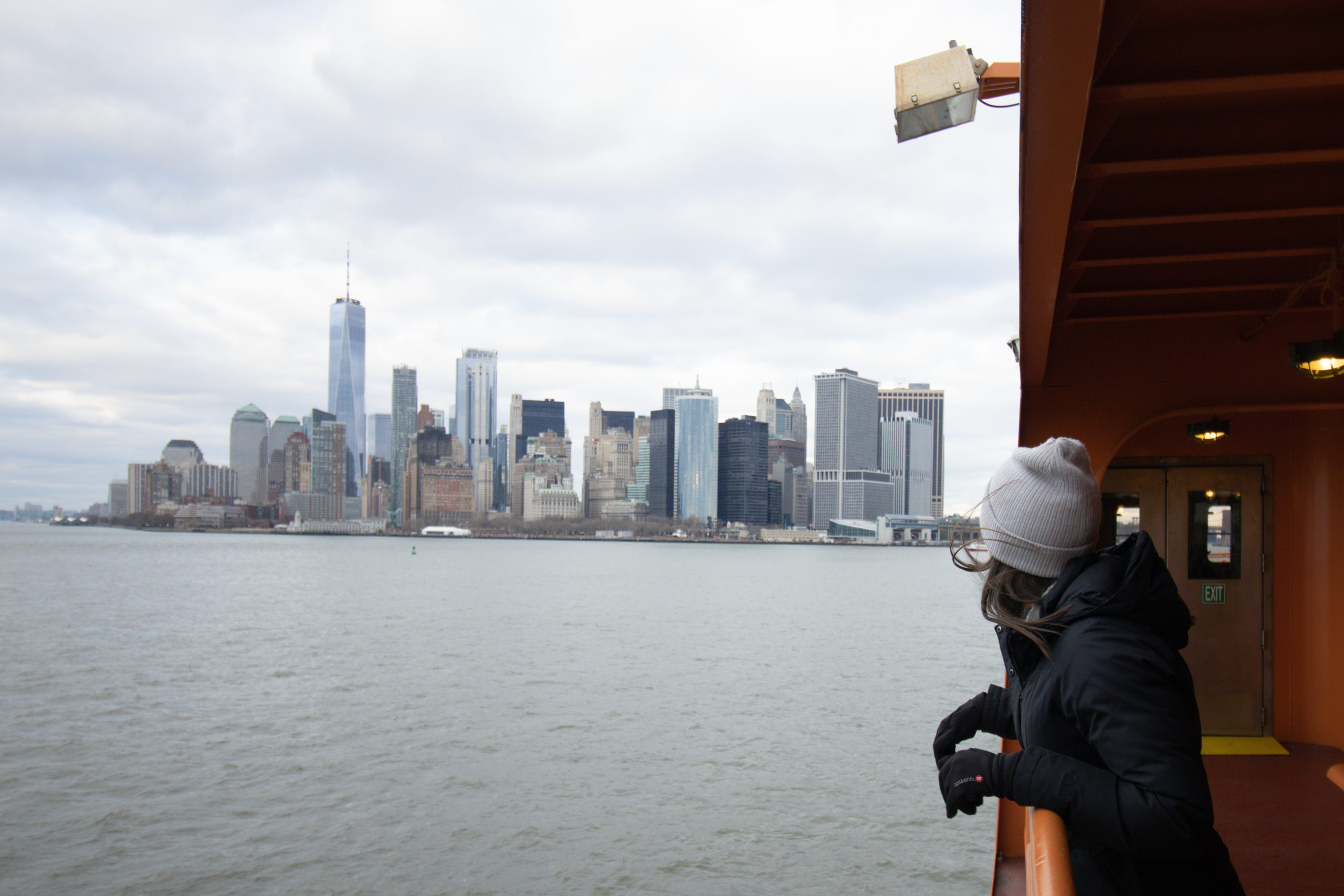 A woman standing on the Staten Island Ferry with the Manhattan skyline view in the background.