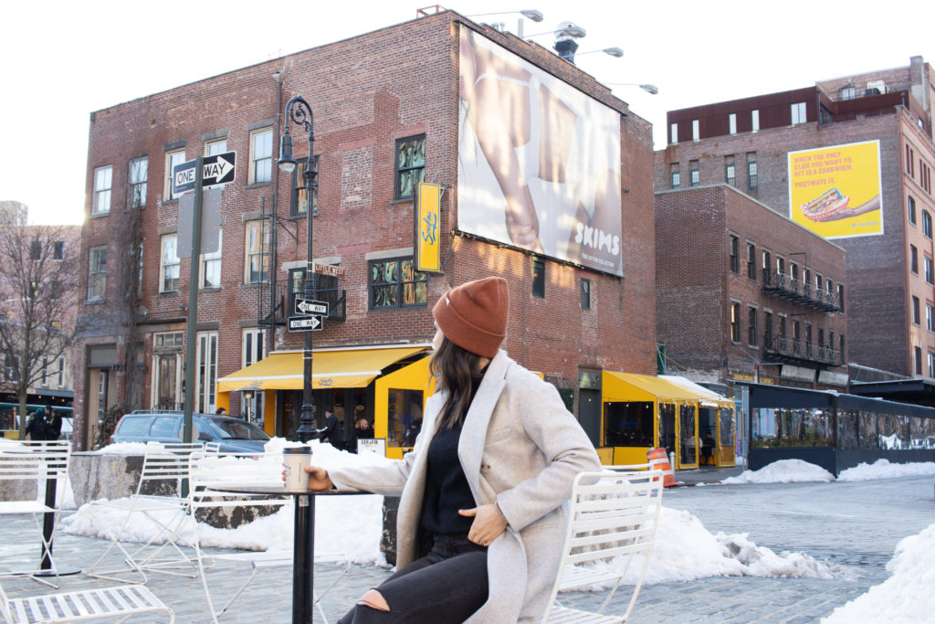 Woman sitting in Gansevoort Plaza for an instagram photo