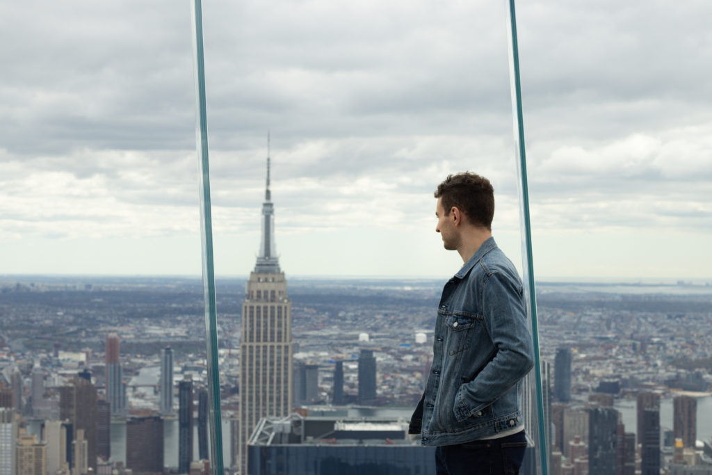 Man posing on The Edge for Instagram, one of the Instagram spots in NYC