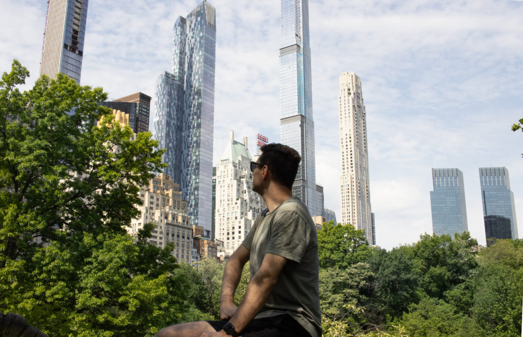 Man looking at Midtown skyline from Central Park in the summer
