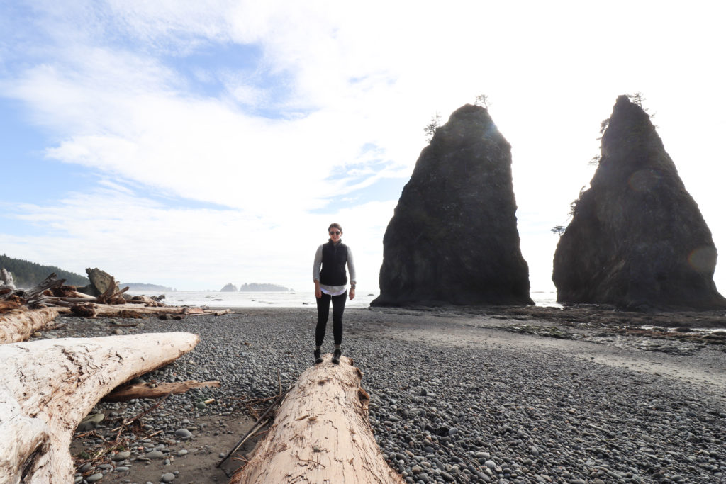 Woman standing on driftwood on ONP beaches