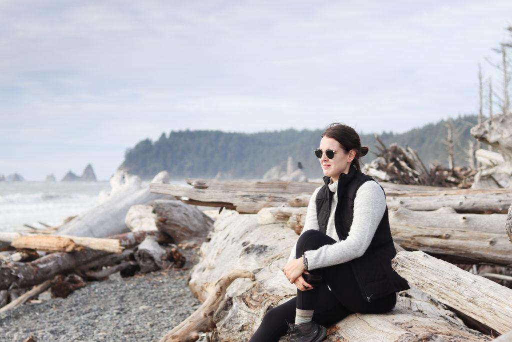 Woman sitting on driftwood log at Rialto Beach