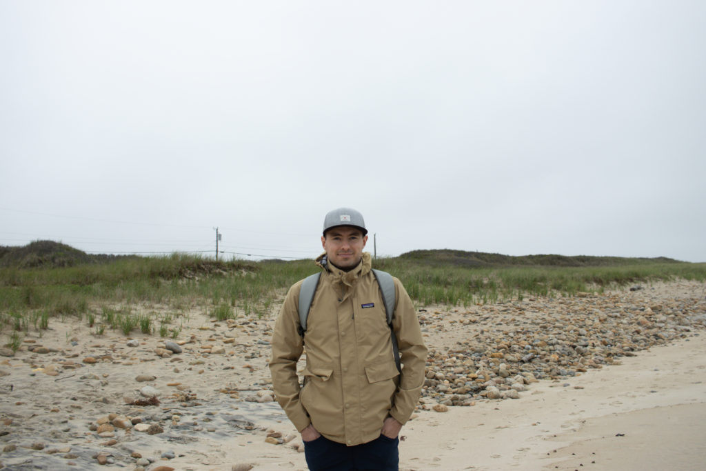 Man standing along the shoreline at A view of the shoreline at one of the Martha's Vineyard beaches