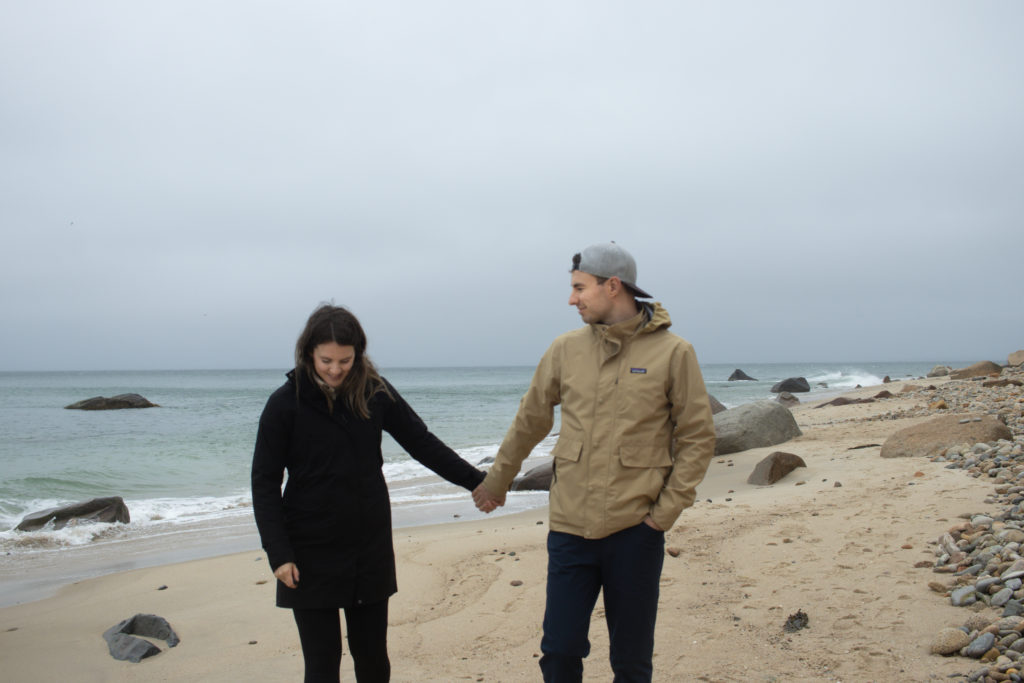 A couple holding hands at A view of the shoreline at one of the Martha's Vineyard beaches