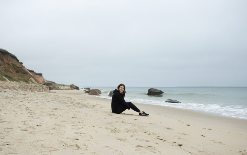 A women sitting on a sandy shore of one of the Martha's Vineyard beaches