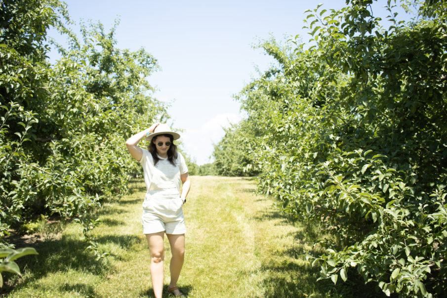 Woman standing in an orchard at Angry Orchard