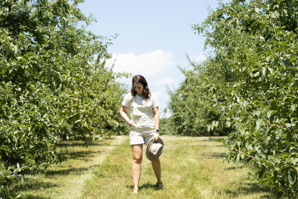 Woman walking in Angry Orchard orchard